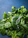 Grön spenatspirulinasmoothie i murarekrus Arkivfoto