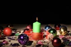 Grön stearinljus med julstruntsaker Royaltyfria Bilder