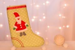 Grön strumpa med Santa Claus för handgjorda gåvaställningar mot bakgrunden av julljus och woolen bollar arkivbild