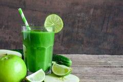 Grön sund smoothie i ett exponeringsglas med spenat, äpplet, gurkan och limefrukt med ett sugrör Detoxdrink arkivbild