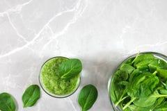 Grön sund smoothie och en bunke av nya spenatsidor med kopieringsutrymme royaltyfri foto