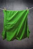 Grön t-skjorta som hänger på rep för att torka arkivfoton