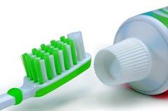 Grön tandborste och tandkräm som isoleras på en vit bakgrund arkivbilder