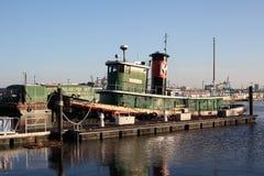 Grön tappningbogserbåt på en jämlike arkivfoto