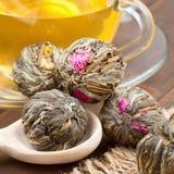 Grön tea klumpa ihop sig med blommor, kuper tea och träskeden Arkivfoton