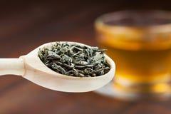 Grön tea lämnar i träsked, kuper av tea Arkivbild