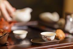 Grön tea med koppen och teapoten Förlagen häller te på vita koppar Arkivfoton