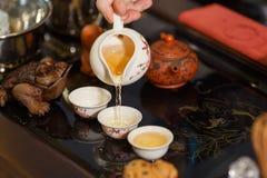 Grön tea med koppen och teapoten Förlagen häller teet på kopparna Royaltyfri Fotografi