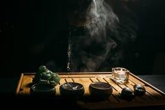 Grön tea med koppen och teapoten Mannen häller varmt kinesiskt te in i tekoppen Royaltyfria Bilder