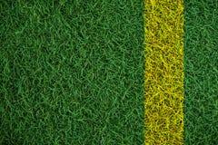 Grön torvagrästextur med den gula linjen, i fotbollfält Arkivbild