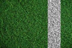 Grön torvagrästextur med den vita linjen, i fotbollfält Arkivbild