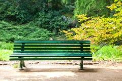 Grön träbänk för tappning i parkera Royaltyfri Bild