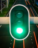 Grön trafikljus med den tomma huvudvägen på bakgrund, begrepp för att gå framåtriktat, positivity, framgång royaltyfri bild