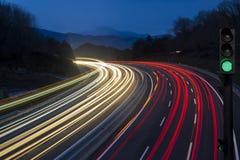 Grön trafikljus med ljusa strömmar från pågående trafik Arkivfoto
