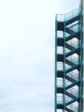 Grön utvändig stege för trappa för brandflykt över molnig himmel Arkivbilder