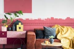 Grön växt i den vita krukan bredvid svarta och guld- vaser på pastellfärgad rosa och burgundy hylla i vardagsrum med ombreväggen  royaltyfri fotografi