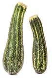 Grön zucchini som två isoleras på vit bakgrund Royaltyfri Bild