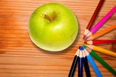 Gröna äpple- och regnbågeblyertspennor på träskrivbordet royaltyfri fotografi