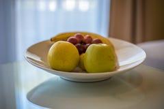 Gröna äpplen, druvor och banan på den vita tabellen Fotografering för Bildbyråer
