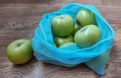 Gröna äpplen i återvinningsbara ecopåsar fotografering för bildbyråer