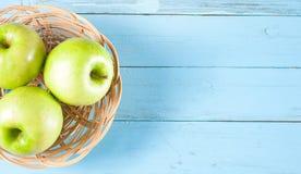 Gröna äpplen i korg på blått trä Royaltyfri Fotografi