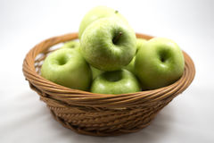 Gröna äpplen i korgen Arkivbild