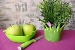 Gröna äpplen med blommor på tabellen Royaltyfri Foto