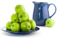 Gröna äpplen och blå kanna Arkivbilder