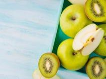 Gröna äpplen och kiwi på turkos Royaltyfri Bild
