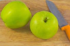 Gröna äpplen och kniv på att hugga av kvarteret Arkivfoto