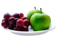 Gröna äpplen och röda druvor Arkivbilder
