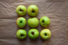 Gröna äpplen på beigapappersbakgrund fotografering för bildbyråer