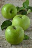 Gröna äpplen på grå bakgrund Arkivfoto