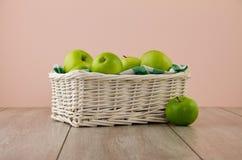 Gröna äpplen på rosa färg Arkivbild