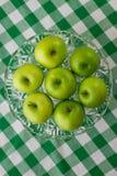 Gröna äpplen på smaragdgingham Royaltyfri Foto