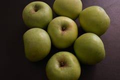 Gröna äpplen på svart bakgrund royaltyfria bilder