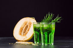 Gröna alkoholcoctailar Förkylningdrinkar och en melon på en svart bakgrund Drinkar med dragon, is och den söta melon kopiera avst Royaltyfri Bild