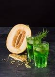 Gröna alkoholcoctailar Förkylningdrinkar och en melon på en svart bakgrund Drinkar med dragon, is och den söta melon kopiera avst Royaltyfria Foton