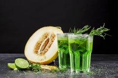 Gröna alkoholcoctailar Förkylningdrinkar och en melon på en svart bakgrund Drinkar med dragon, is och den söta melon kopiera avst Fotografering för Bildbyråer