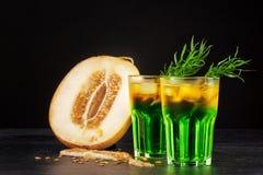 Gröna alkoholcoctailar med melonskivor Förkylningdrinkar och en melon på en svart bakgrund Drinkar med dragon, is och Royaltyfri Foto