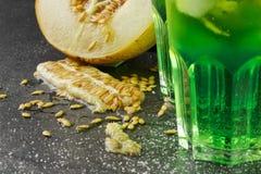 Gröna alkoholcoctailar, närbild Förkylningdrinkar och en melon på en svart bakgrund Drinkar med dragon, is och den söta melon arkivfoton