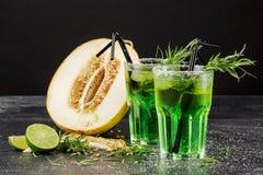 Gröna alkoholcoctailar Sommardrinkar och en snittmelon på en svart bakgrund Drinkar med kopieringsutrymme för dragon, för is och  Arkivbild