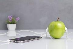 Gröna Apple med hörlurar med mikrofon förbindelse till telefonen Royaltyfri Bild