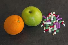Gröna Apple och apelsin bredvid vitaminminnestavlorna och supplemenna Royaltyfri Foto