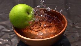 Gröna Apple som faller till vattnet i träbunke lager videofilmer