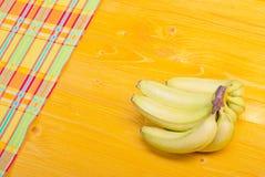 Gröna bananer i den lägre vänstersidan tränga någon till det övre högra hörnet Arkivfoto