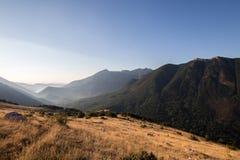 Gröna berg med gula gräsfält och sjö i backgroen Arkivfoton