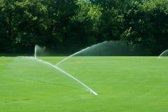 gröna bevattna sprinklers för fältgräs royaltyfria bilder