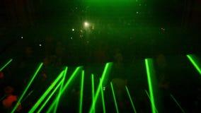 Gröna blinkastrålar från laser-show i fullsatt nattklubb på allhelgonaaftonen festar arkivfilmer