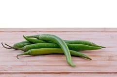Gröna chili på skärbräda Royaltyfri Fotografi